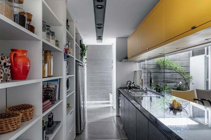 Cozinha pequena moderna com armário amarelo.