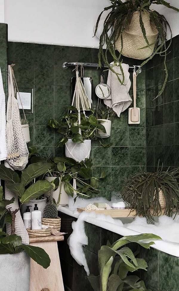 Banheiro moderno com vasos de plantas e revestimento de granito verde ubatuba.