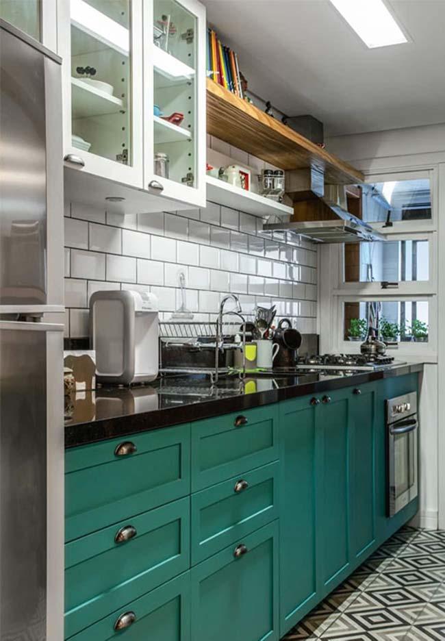Cozinha moderna com armário verde e piso decorado.