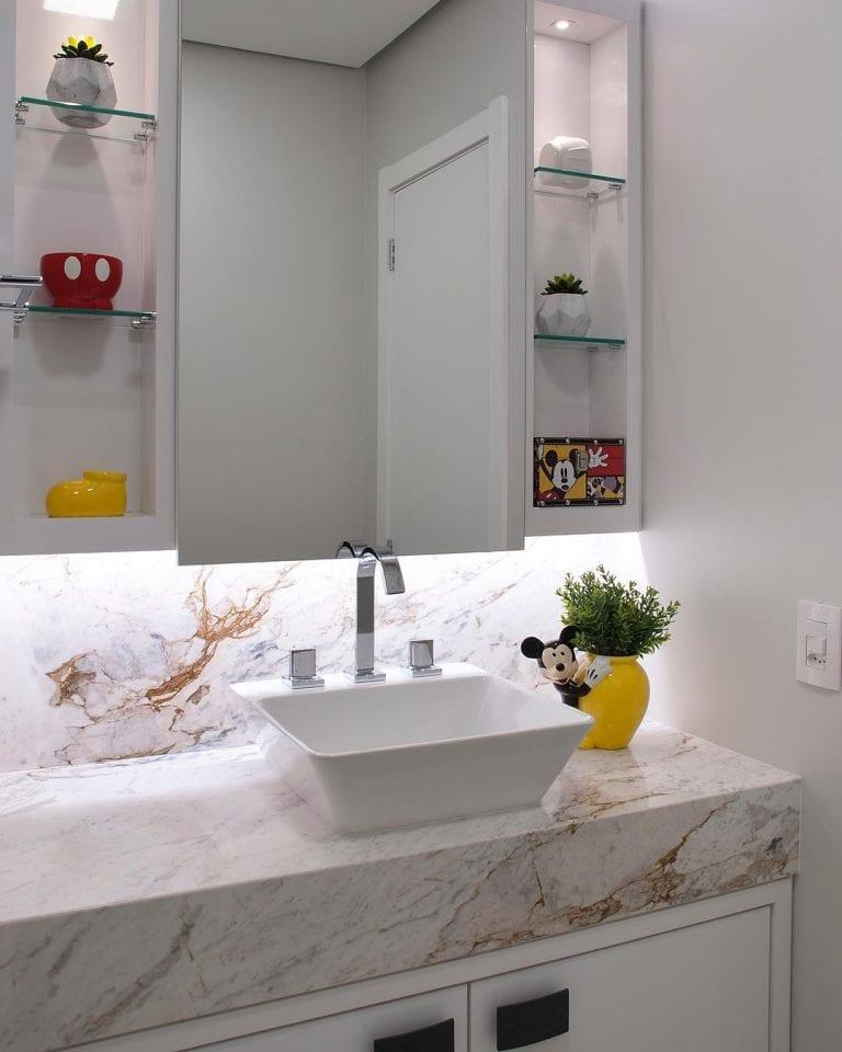 Banheiro pequeno branco com decoração do mickey.
