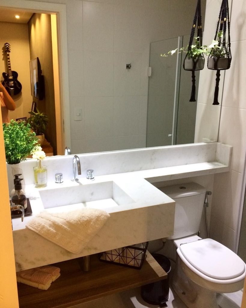 Banheiro pequeno com pia esculpida em mármore branco espírito santo.
