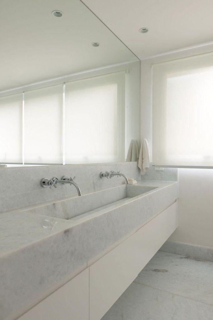 Banheiro com pia esculpida de mármore thassos.