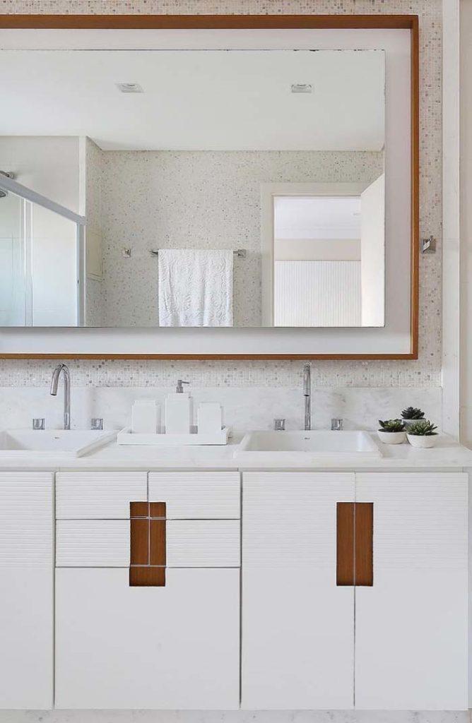 Banheiro de casal branco com bancada de mármore piguês.