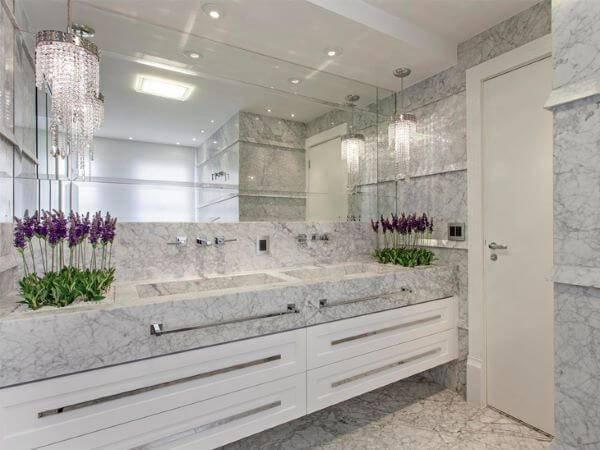 Banheiro luxuoso com lustre e mármore carrara.