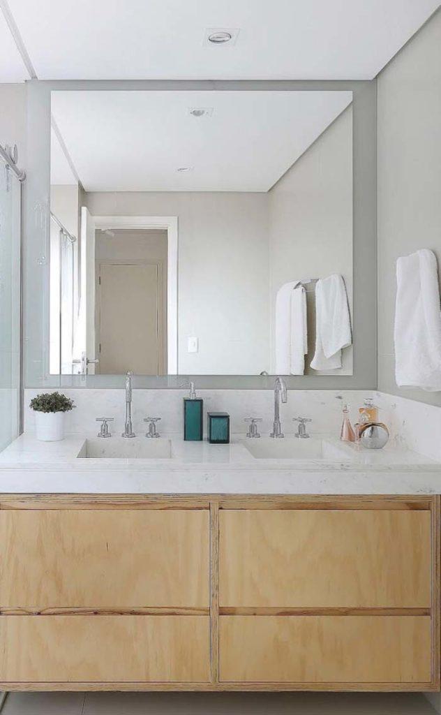 Banheiro de casal com pia esculpida de mármore branco piguês.