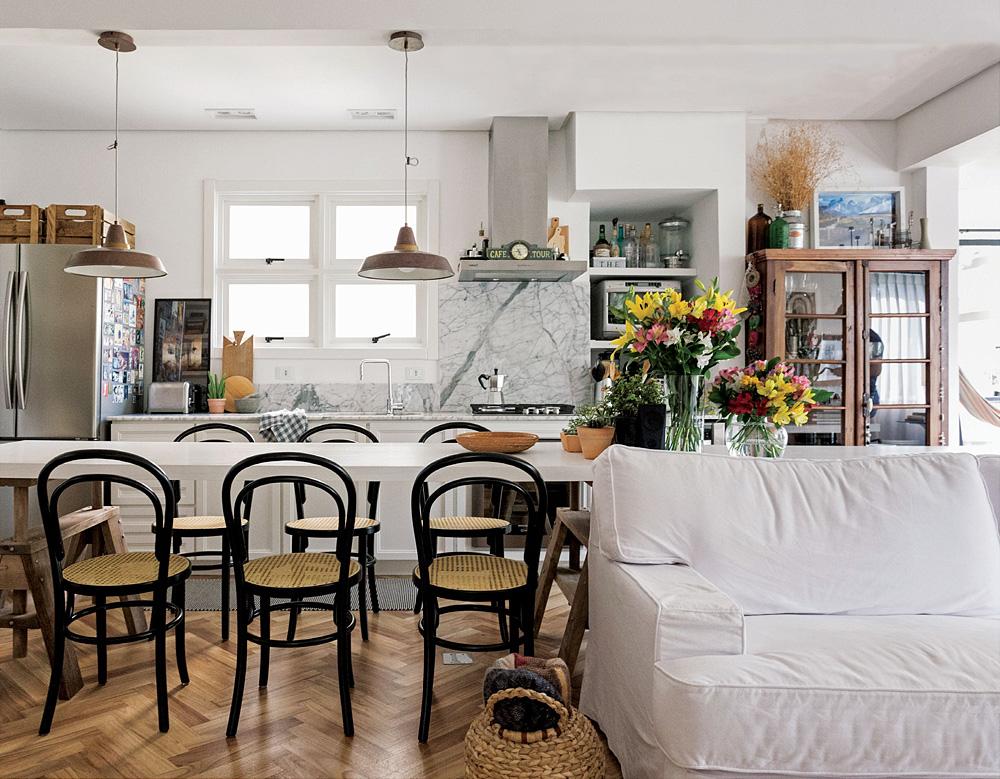 Cozinha aberta com mesa de madeira branca.