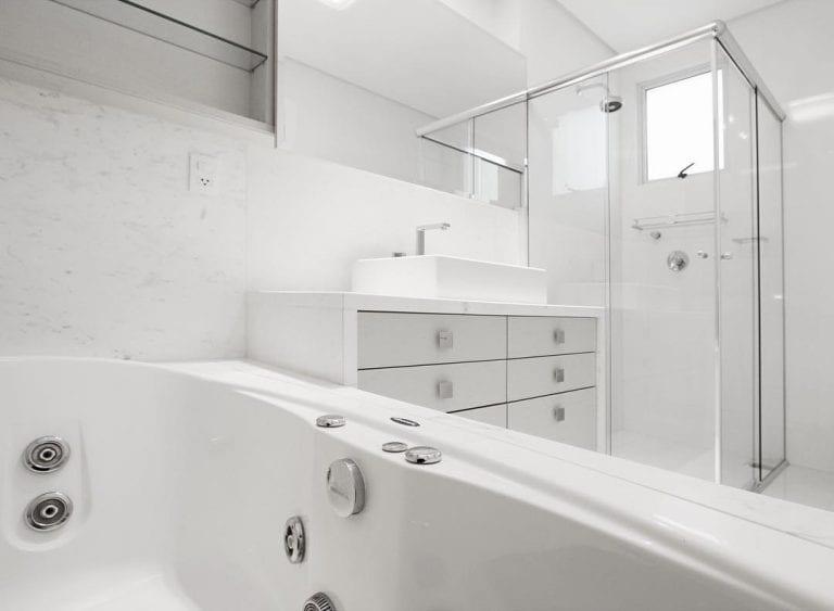 Banheiro luxuoso com bancada e revestimento de mármore piguês.