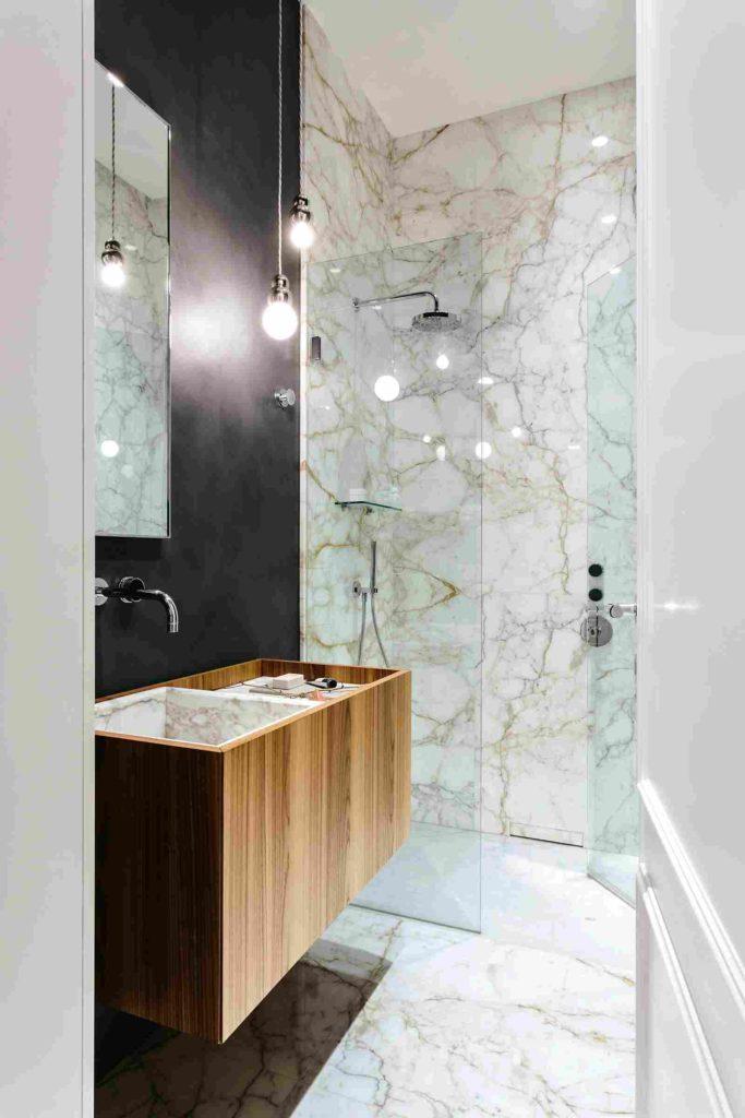 Banheiro luxuoso com pia e revestimento de mármore paraná.