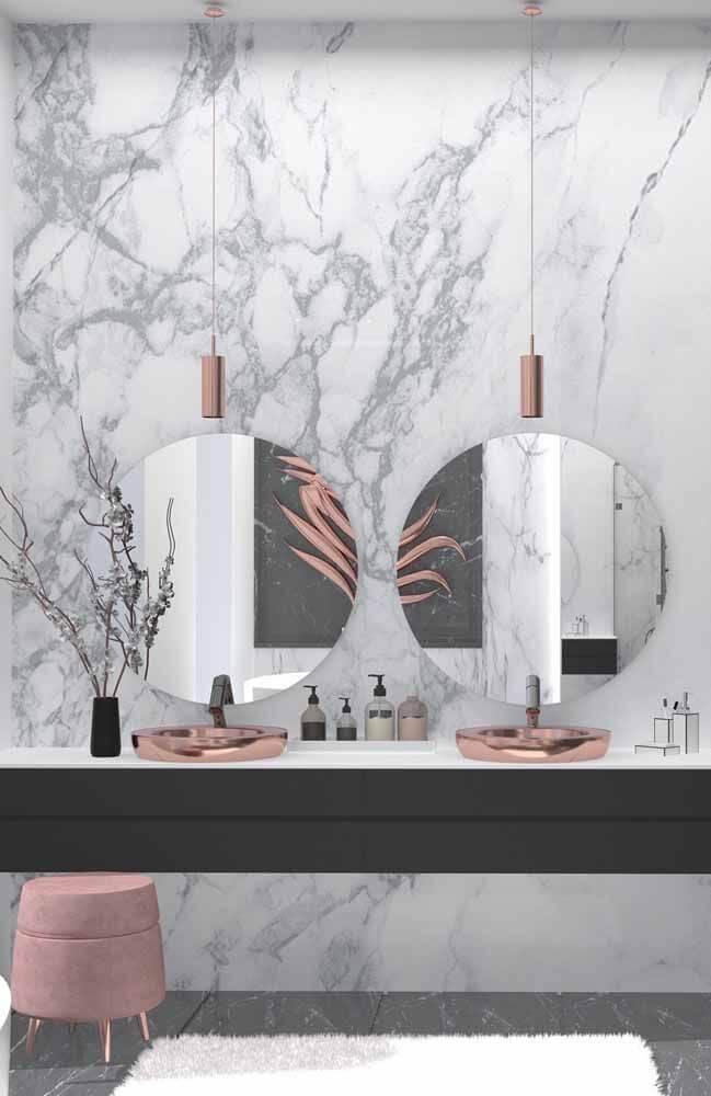 Banheiro feminino luxuoso com cuba de cobre e revestimento de mármore branco carrara.