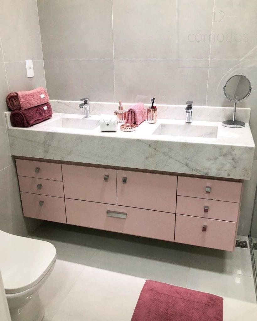 Banheiro feminino com bancada dupla e armário rosa.
