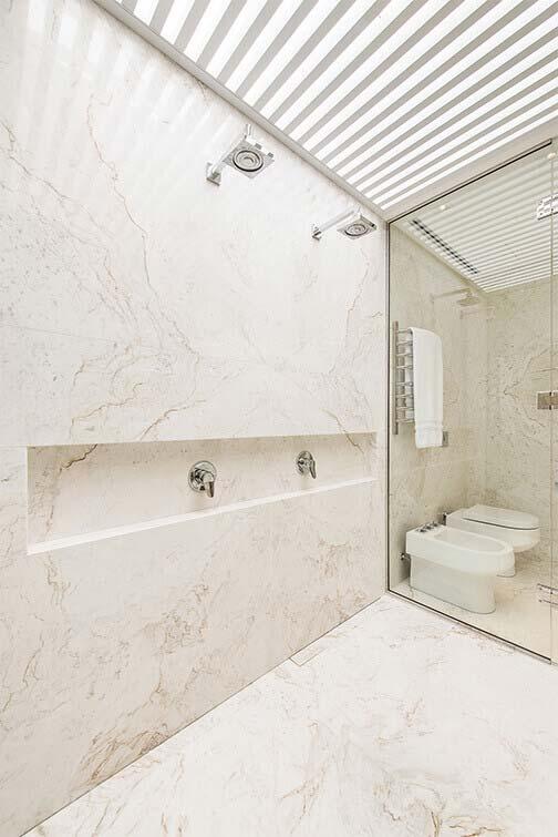 Banheiro com box duplo e revestimento de mármore paraná.