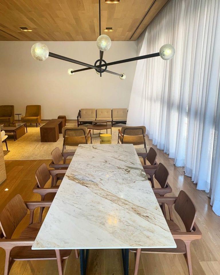 Sala de reuniões com mesa com tampo de mármore branco catalacatta.