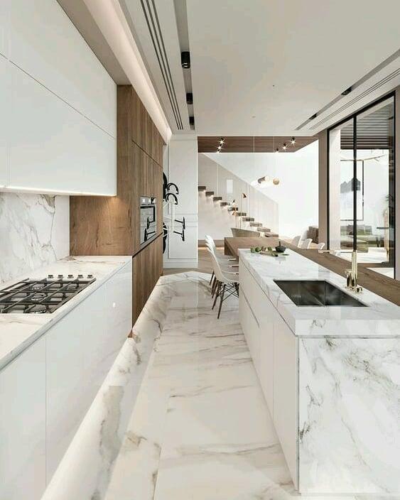 Cozinha americana luxuosa com piso e revestimento de mármore.