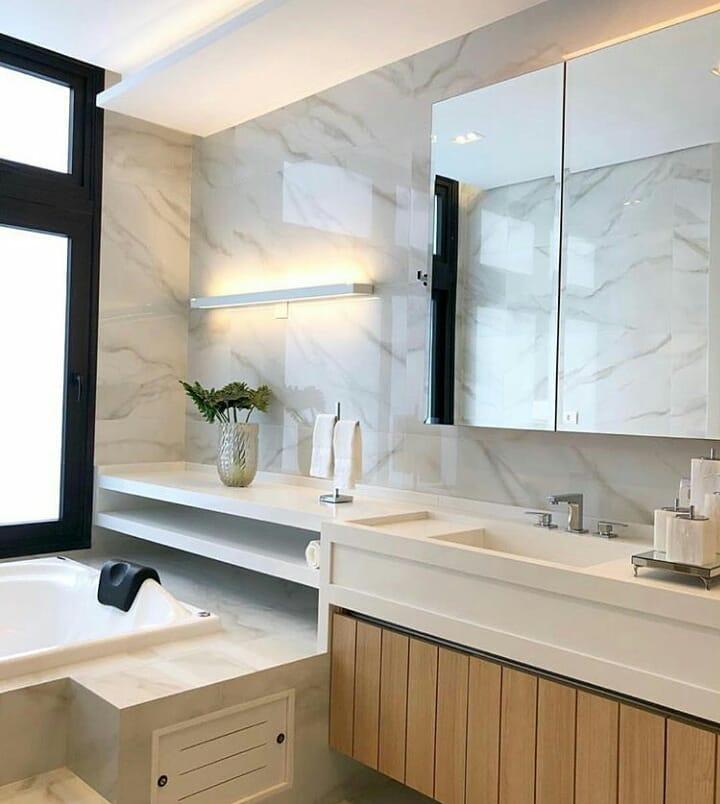 Banheiro luxuoso com revestimento de mármore.