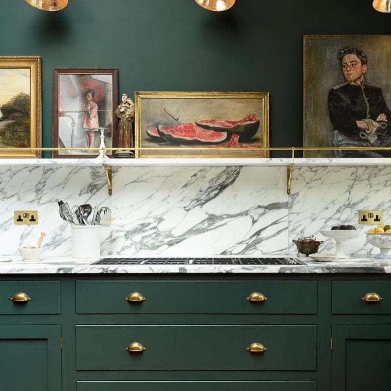 Cozinha luxuosa com armário verde e obras de arte.