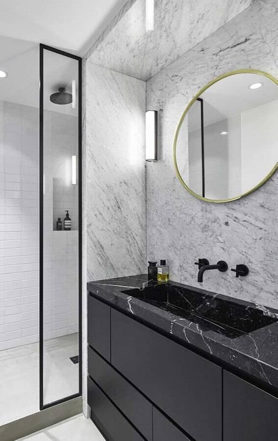 Banheiro moderno com revestimento de mármore branco e bancada de mármore preto.
