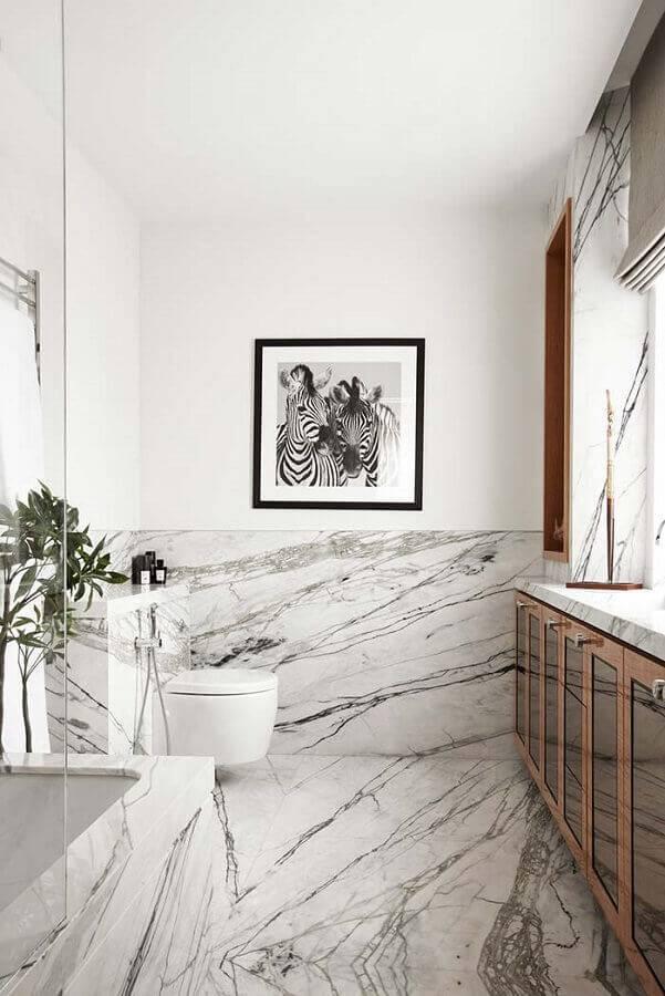 Banheiro luxuoso com banheiro e revestimento de mármore branco carrara.