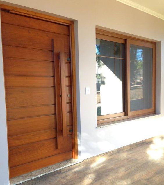 Fachada com porta de madeira e janela de correr.