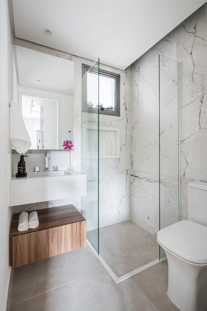 Banheiro branco com revestimento de granito.