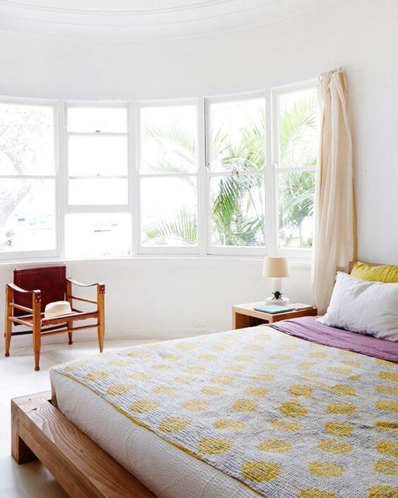 Quarto minimalista com cama de madeira.