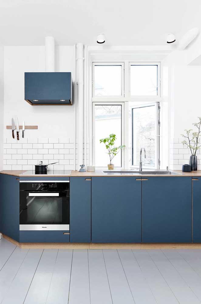 Cozinha escandinava com armários azuis e azulejo de tijolinho branco.