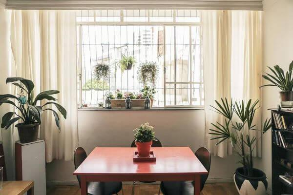 Sala simples com janela de correr com grade.
