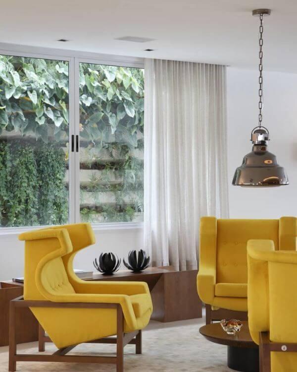 Sala moderna com poltronas amarelas e pendente suspenso.