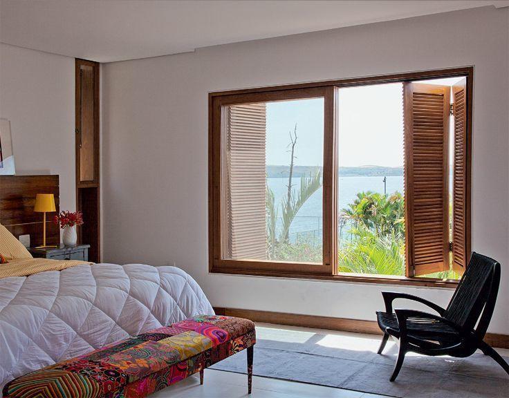 Quarto praiano com janela sanfonada de madeira.