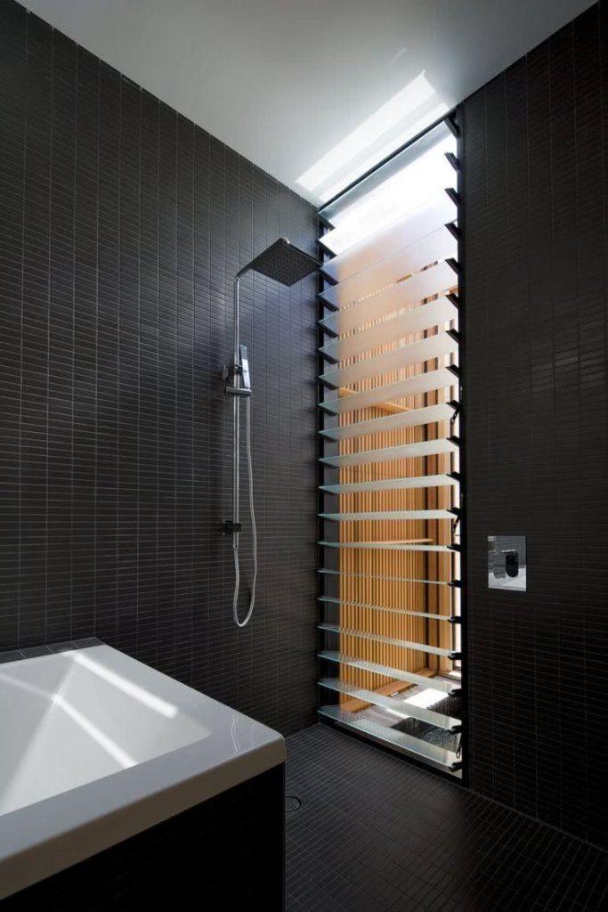 Banheiro preto moderna com janela basculante.