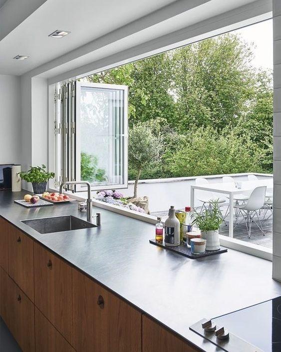 Cozinha moderna com janela de vidro sanfonada.