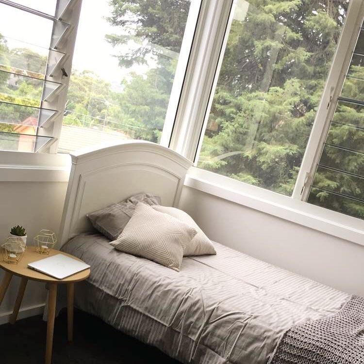 Quarto de solteiro com janela basculante.