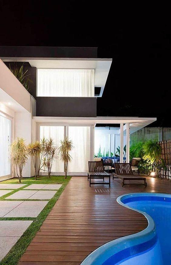 Quintal com deck em em volta da piscina.