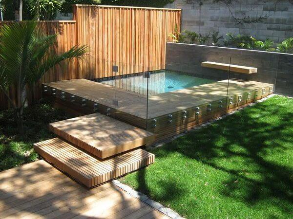 Piscina pequena com deck de madeira com parede de vidro.