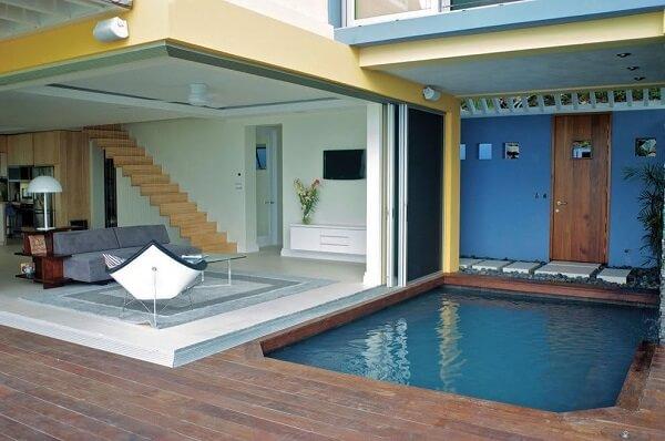 Piscina pequena com deck de madeira e sala aberta.