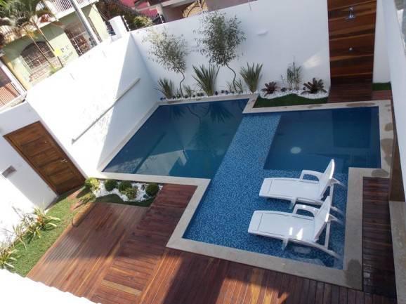 Área externa com chuveiro e deck de madeira.