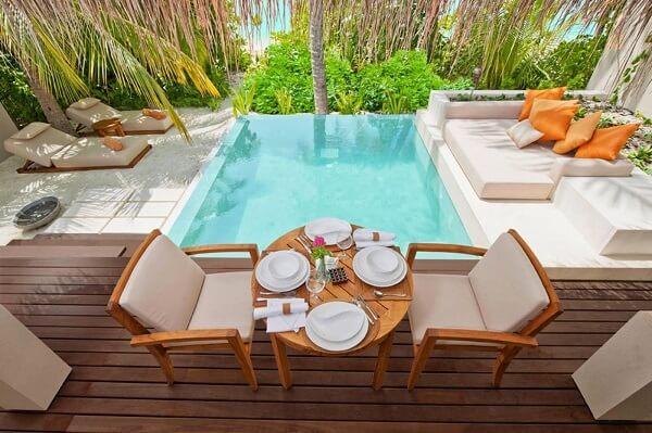 Área externa com espaço de convivência e piscina pequena com borda infinita.