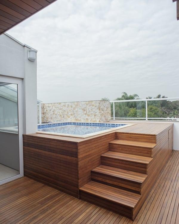 Piscina pequena quadrada com deck de madeira elevado.