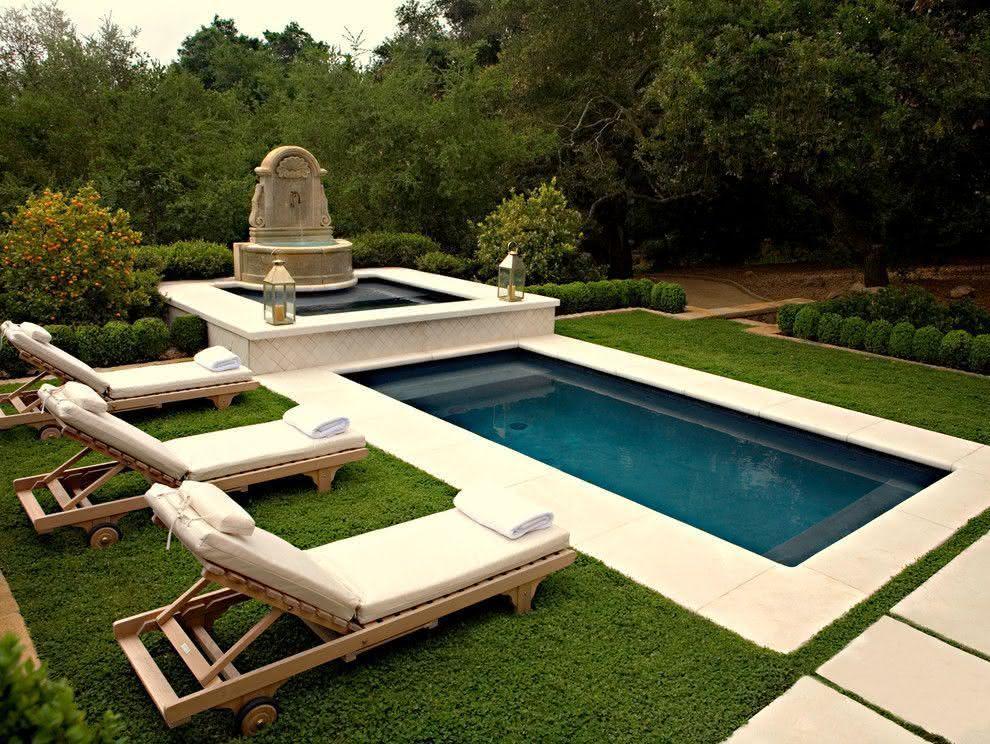 Jardim com fonte e piscina pequena.