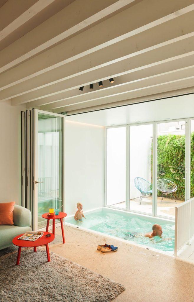 Sala com piscina pequena coberta.