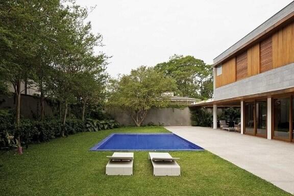 Jardim com piscina pequena e espriguiçadeiras modernas.