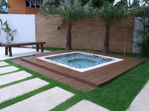 Piscina pequena com deck de madeira e jardim.