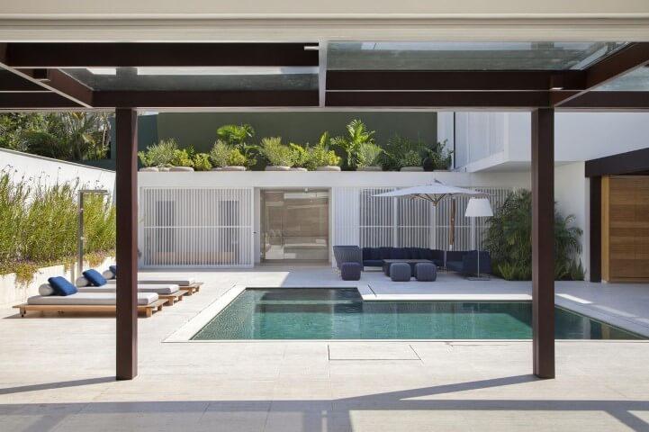 Área externa com espreguiçadeiras modernas e sofás.