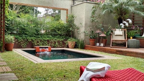 Jardim com piscina pequena e fonte.