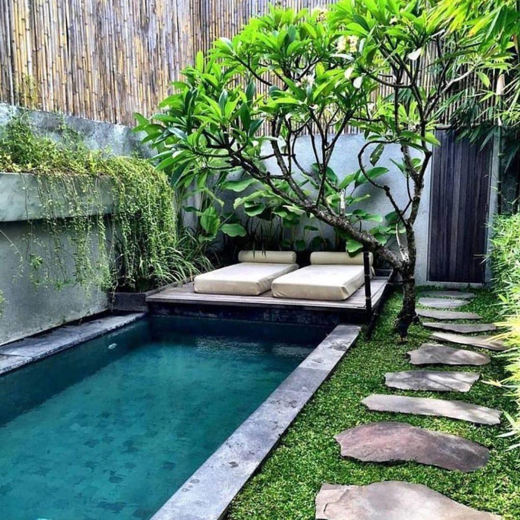 Jardim exuberante com espécies tropicais e área de lazer.