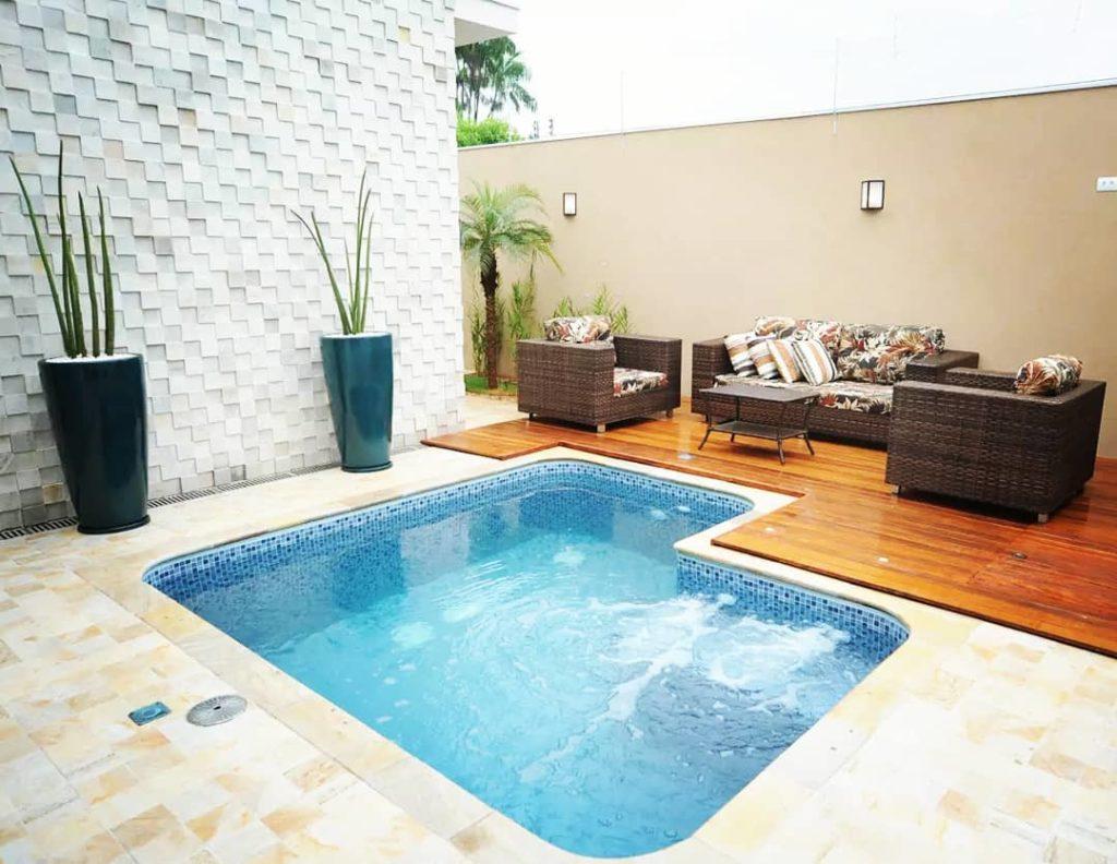 área com sofás de vime e piscina pequena de vinil.