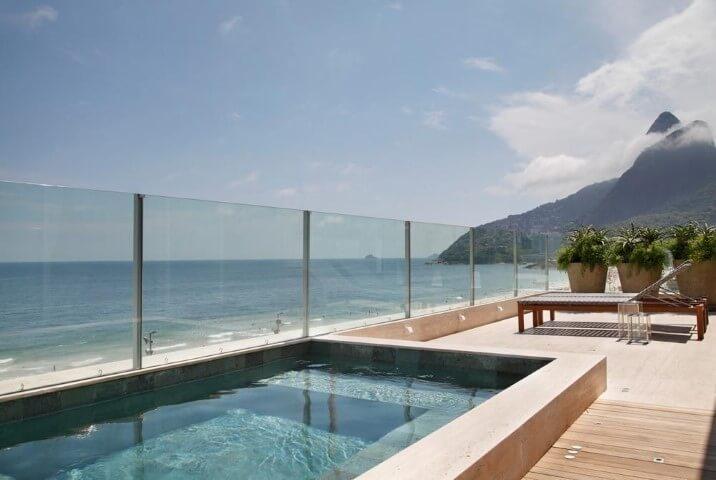 Terraço com piscina pequena e vista para o mar.