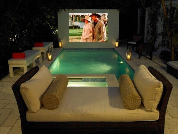 Área externa com piscina pequena e cinema.