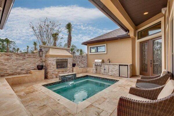 Área externa com churrasqueira e espaço para banho.