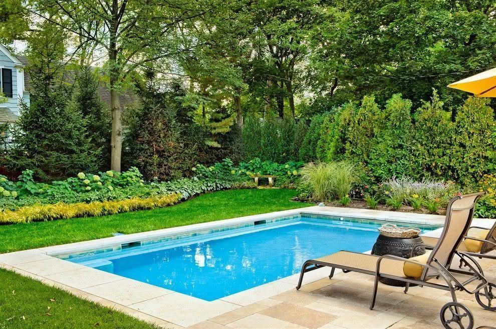 Jardim com piscina pequena e espreguiçadeiras de ferro.