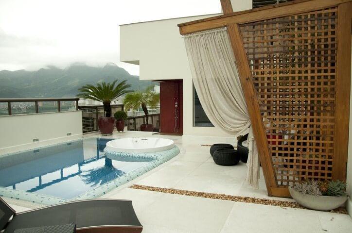 Área externa com piscina de vinil e espaço de descanso.
